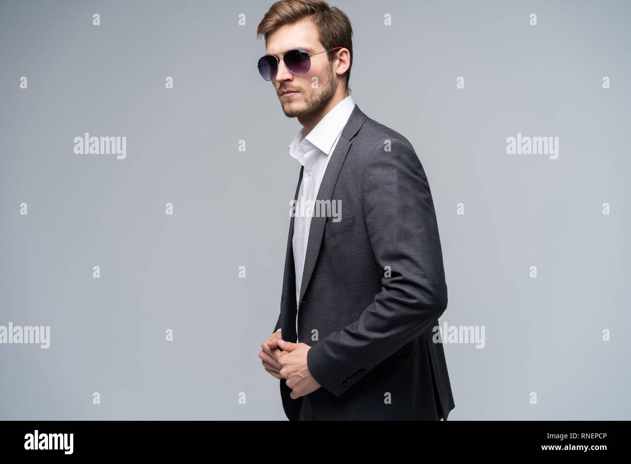 ef517861ea3f Feeling free and comfortable in his style. Handsome young man in full suit  and sunglasses moving in front of gray background.