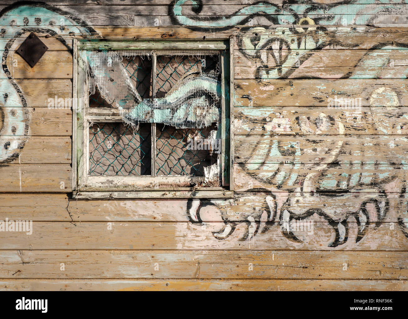 The side of an old and abandoned gypsy caravan with a dragon painting on the side of it, on the shores of Loch Ness, Scotland - Stock Image