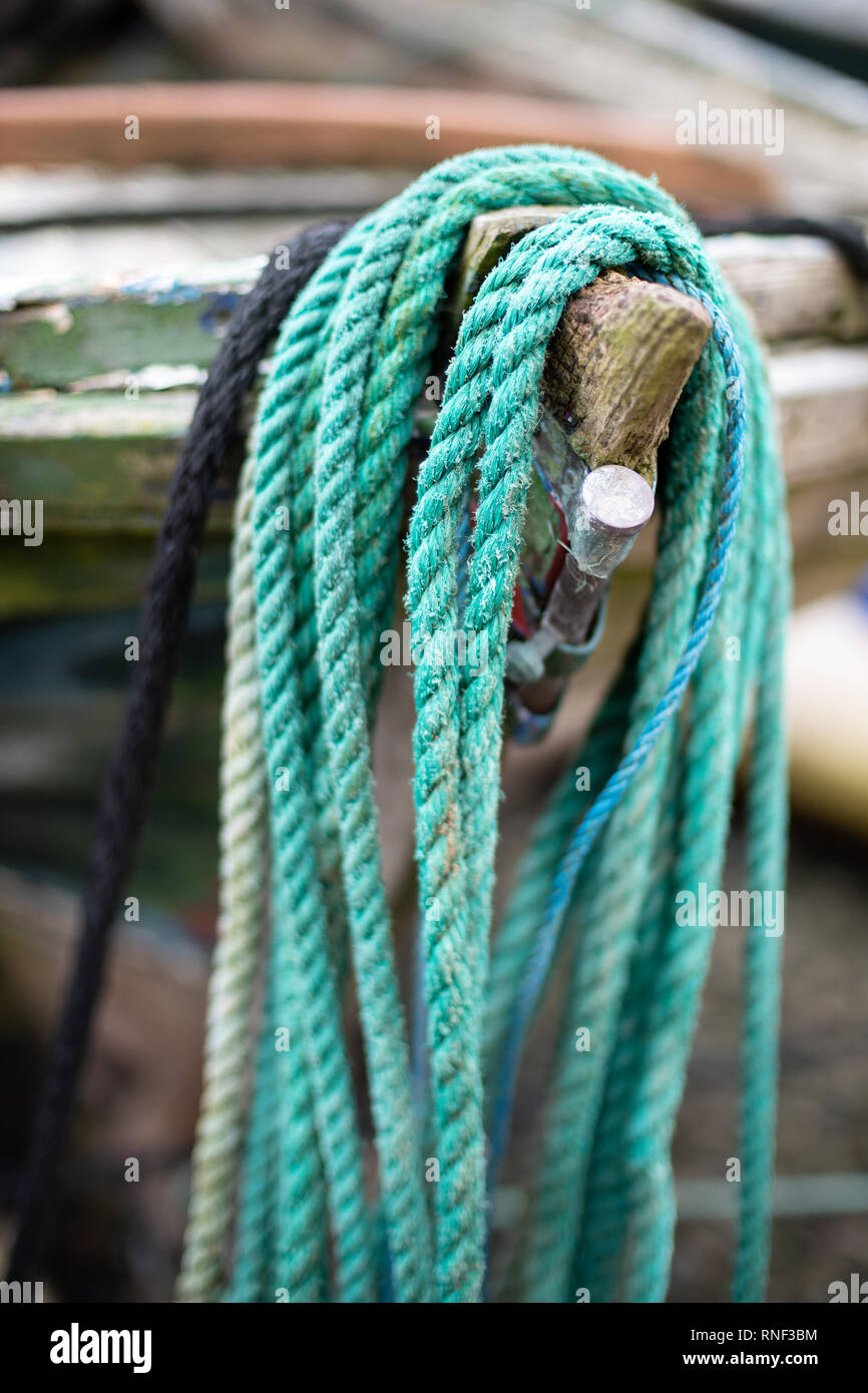 A green nylon mooring rope placed over the bow of a small fishing boat in Gardenstown harbour, Aberdeenshire. - Stock Image