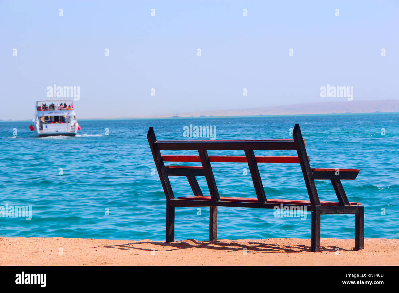 Empty bench near sea and shipped ship. Loneliness. Departure of ship. Bench near beach. Unjustified expectations. Exotic relaxation. Holiday concept - Stock Image