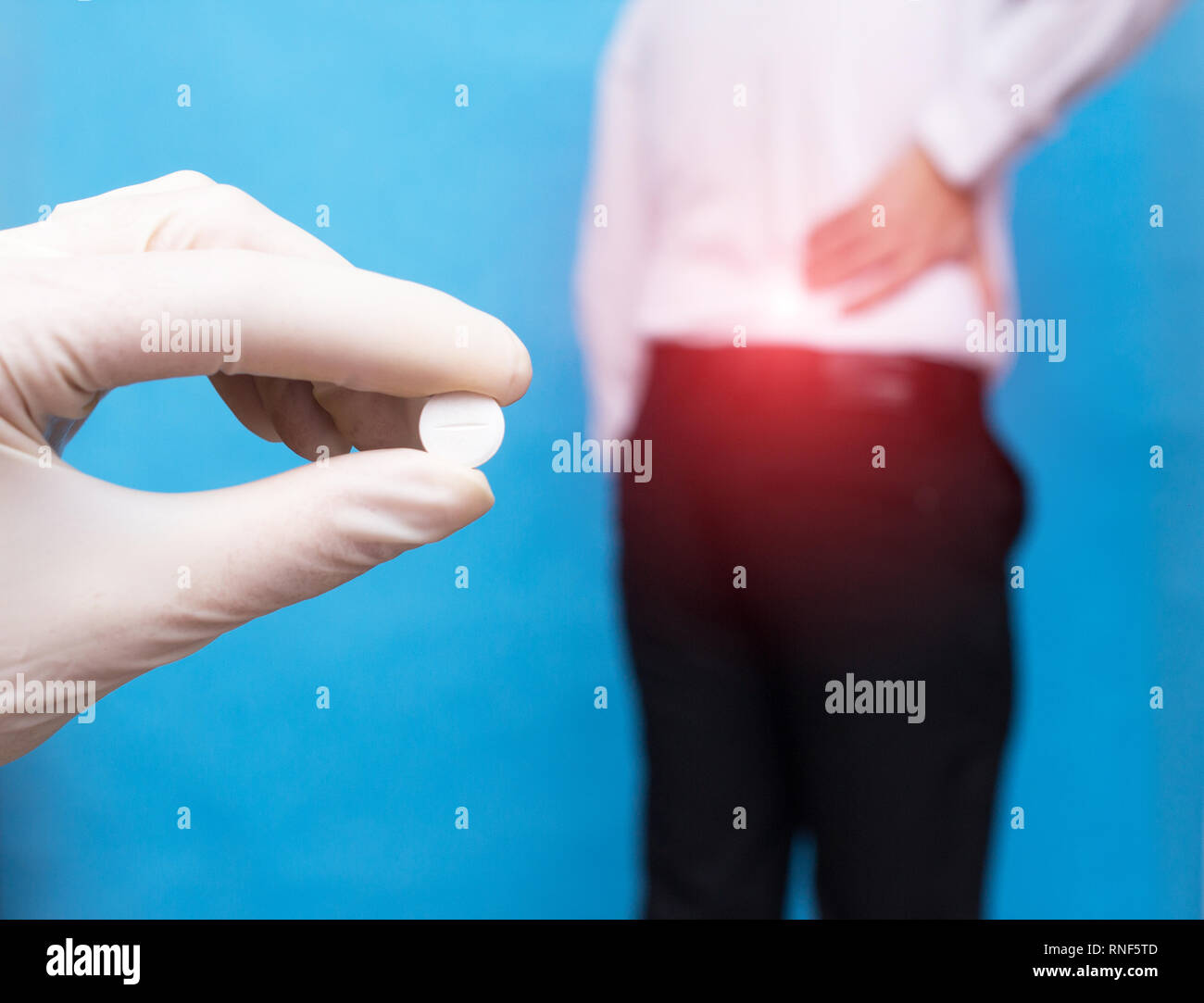 The doctor holds a pill for back pain, in the background is a man who has a backache, an intervertebral hernia and osteochondrosis, sciatica, anti-inf - Stock Image