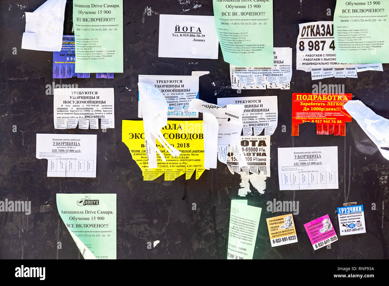 Samara, Russia - May 5, 2018: Live bulletin board. Paper ads on the wall. Shreds of various ads on an old wooden wall - Stock Image
