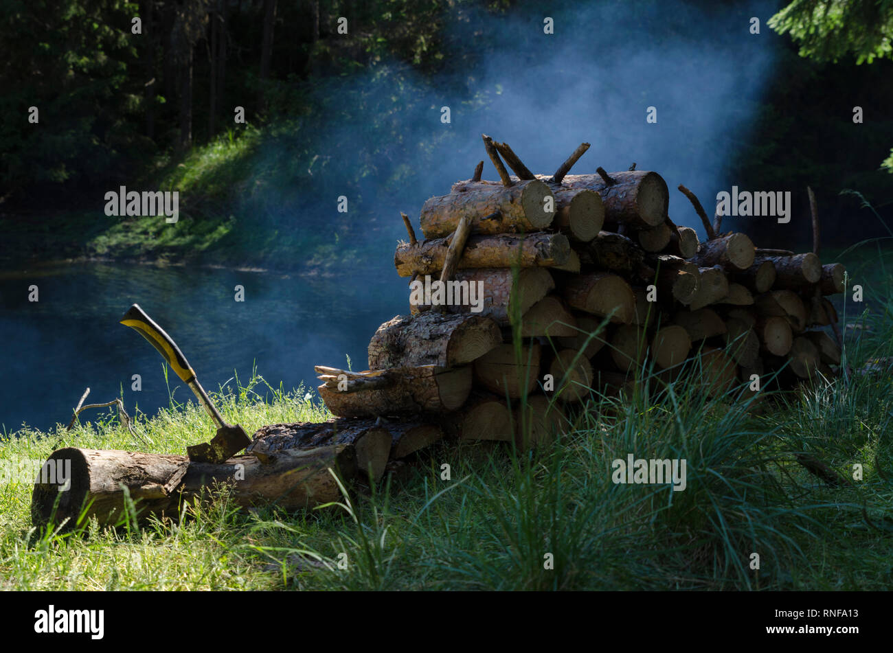 Pile of timbers and axe in a camp area around the lake in mountain. Selective focus - Stock Image