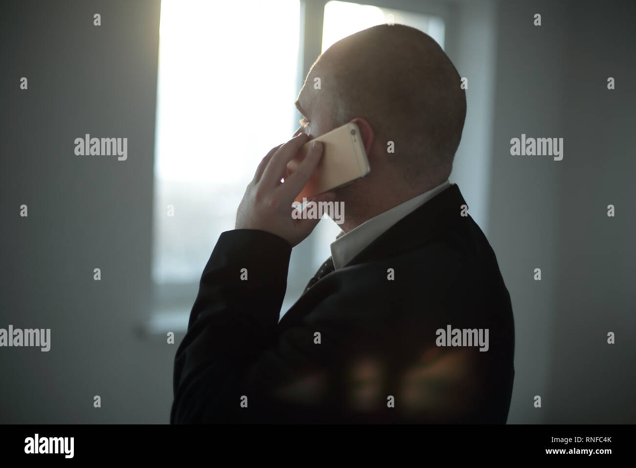 close up. businessman talking on smartphone, on blurred background of office window. - Stock Image