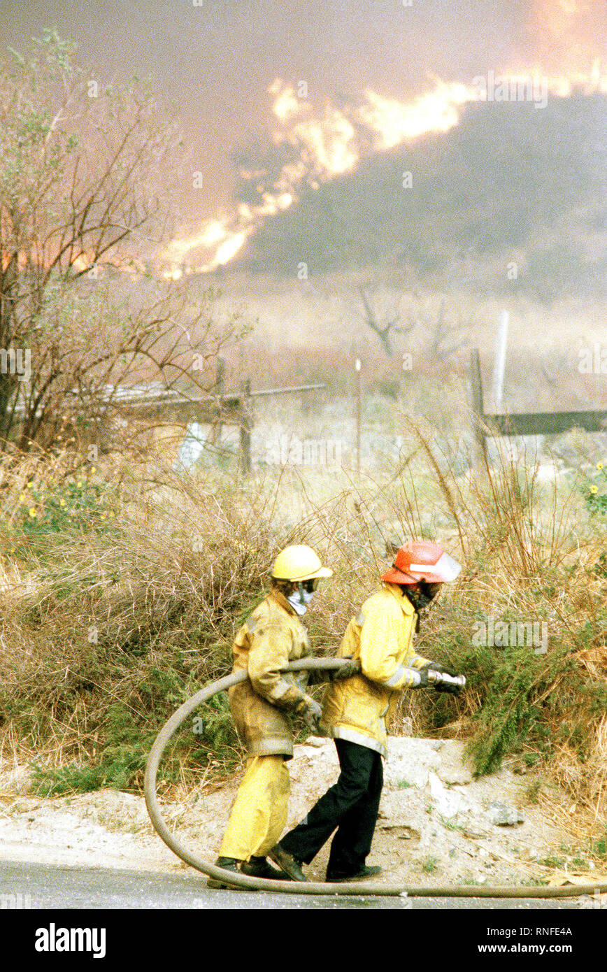 Firefighters battle fires in farmland during the four-day Panorama brush fire, which started in canyons north of town and has been whipped out of control by 40-50 mph winds. Stock Photo