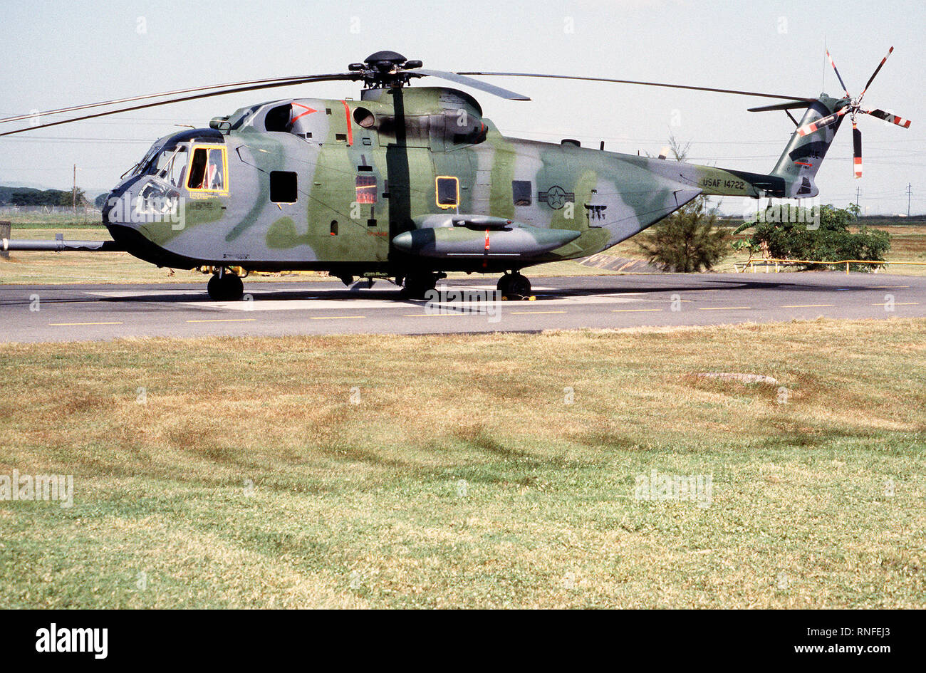 Left side view of a HH-3E Jolly Green Giant helicopter parked on the runway apron. - Stock Image