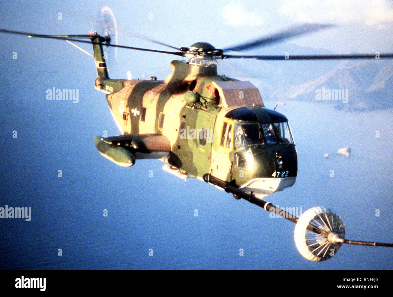 Right front view of a HH-3E Jolly Green Giant helicopter refueling from another aircraft while in flight. - Stock Image