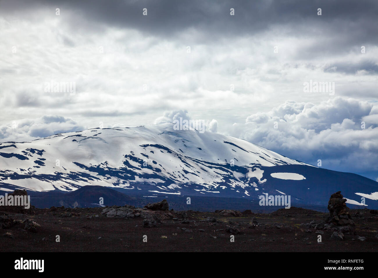 Dramatic sky over snow capped Hekla (Hecla) stratovolcano, one of Icelands most active volcanoes and popular tourist attraction in Southwestern Icelan - Stock Image