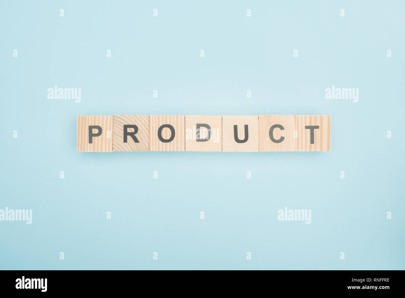 top view of product lettering made of wooden cubes on blue background - Stock Image