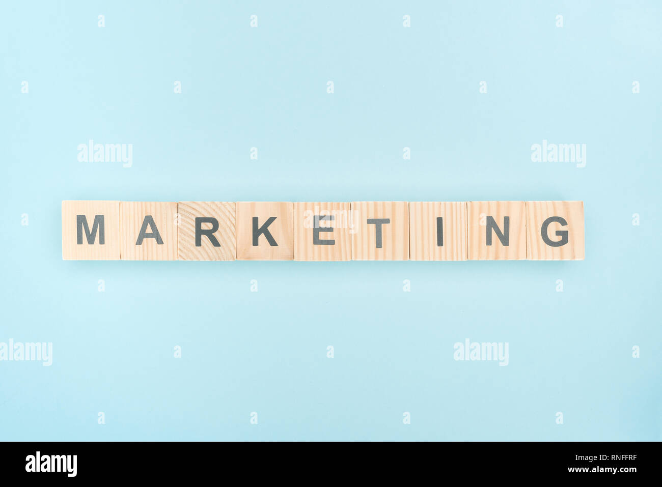 top view of marketing lettering made of wooden cubes on blue background - Stock Image