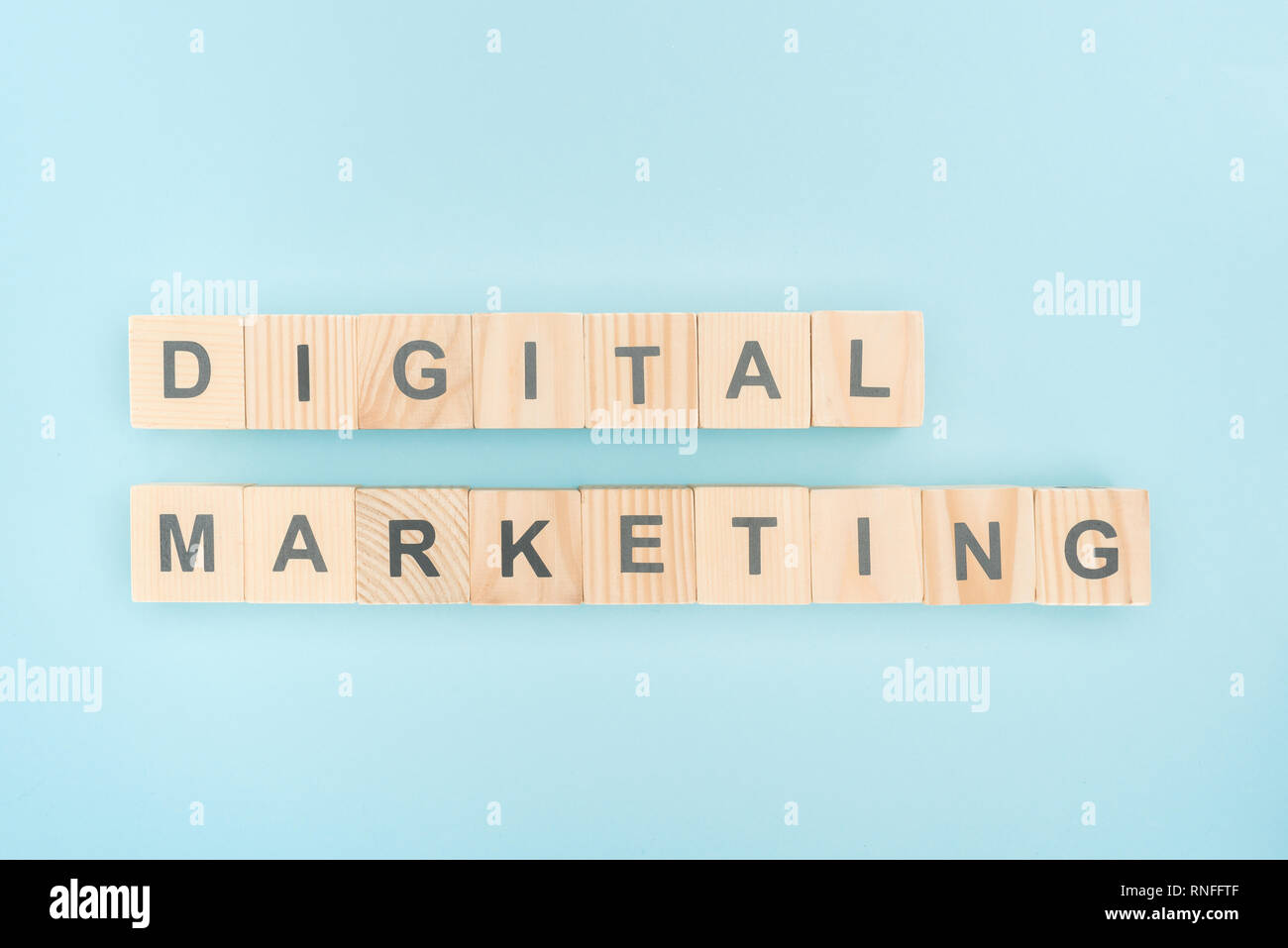 top view of digital marketing lettering made of wooden cubes on blue background - Stock Image