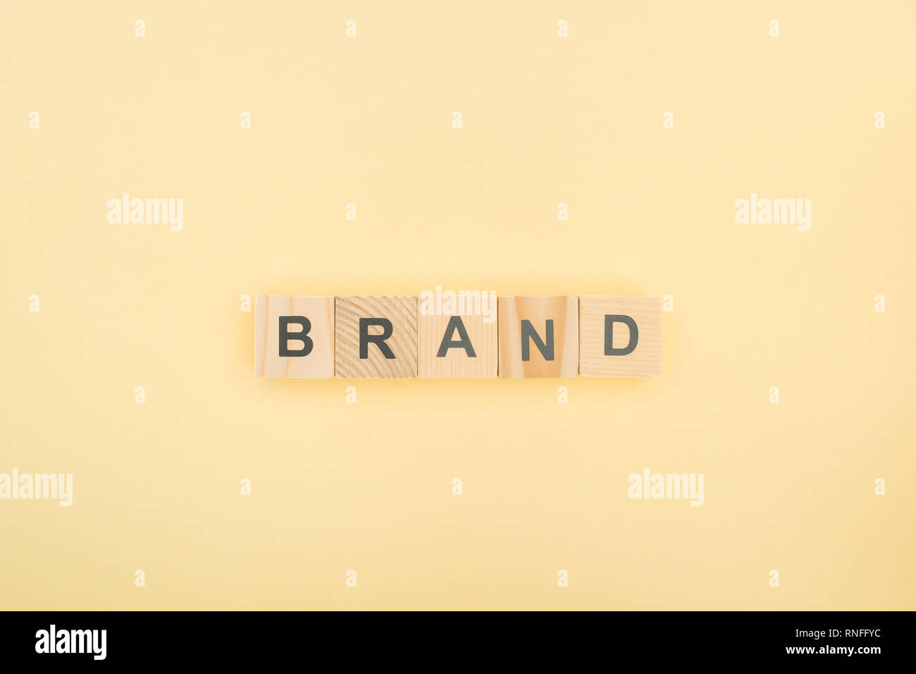 top view of brand lettering made of wooden cubes on yellow background - Stock Image