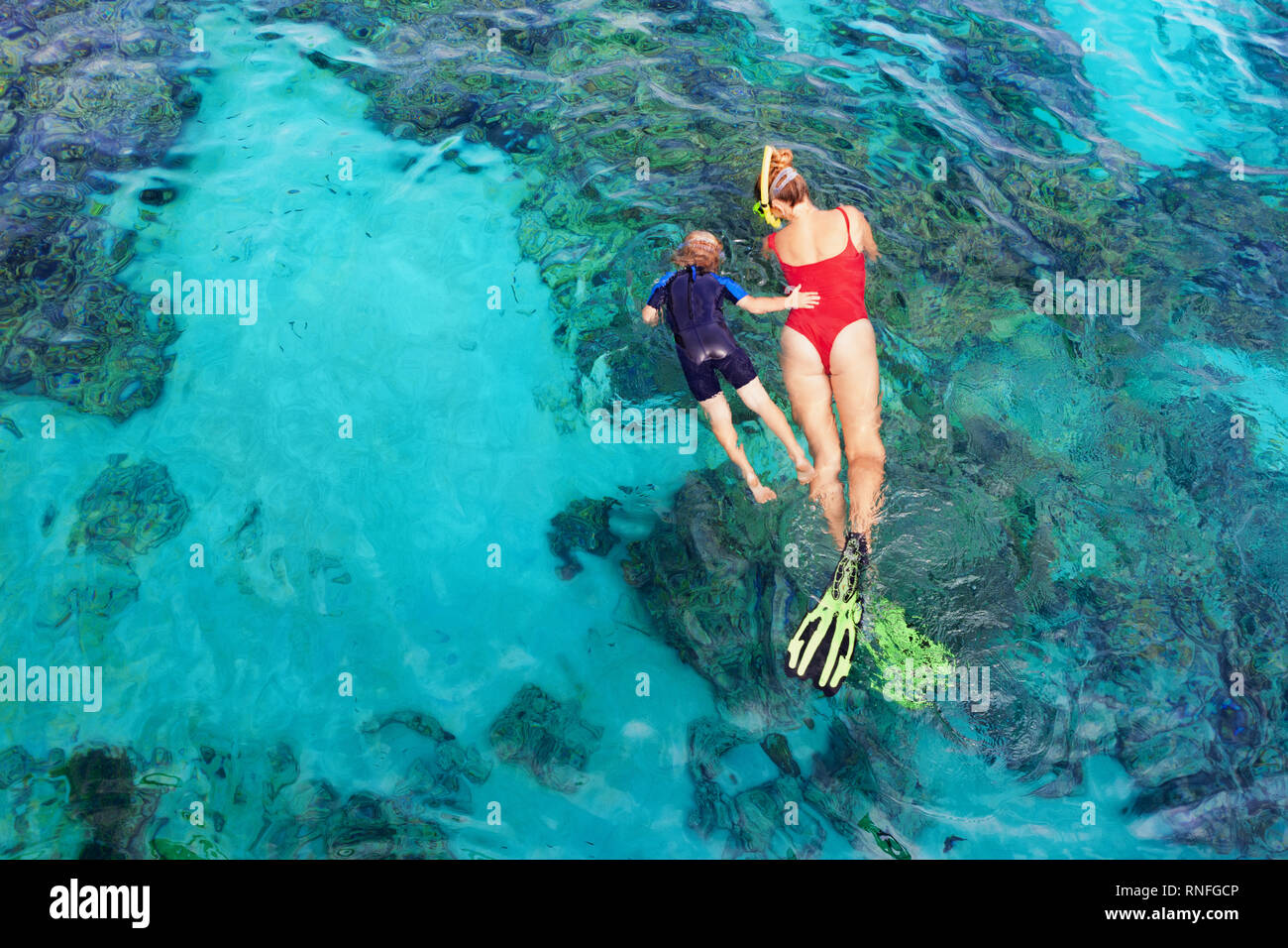 Happy family - mother, kid in snorkeling mask dive underwater, explore tropical fishes in coral reef sea pool. Travel active lifestyle, beach adventur - Stock Image