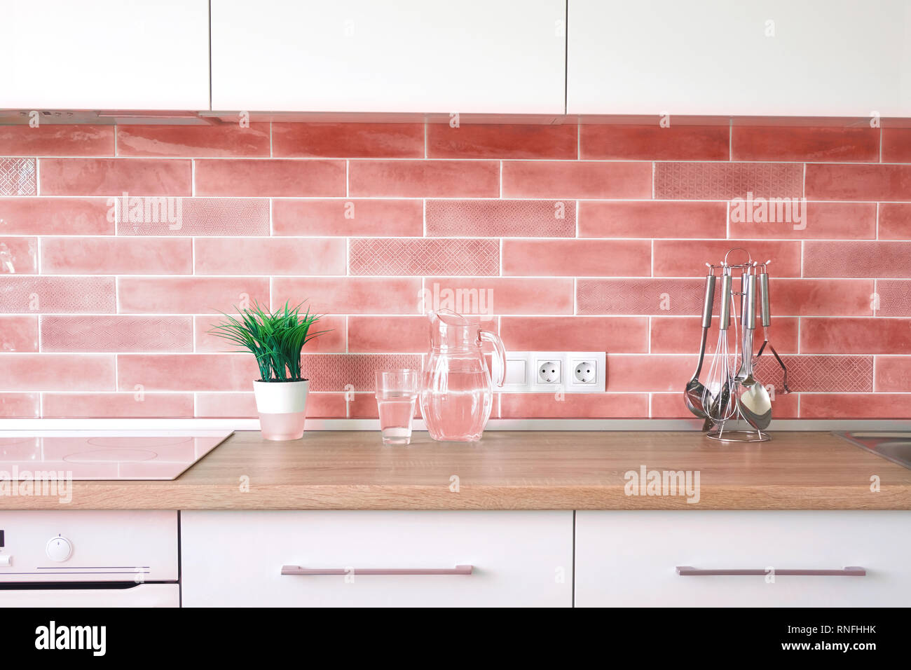 Modern Kitchen At Home With Kitchenware And Flowerpot On A Top And Wall Tiles In A Trend Color Of The Year 2019 Living Coral Pantone Stock Photo Alamy