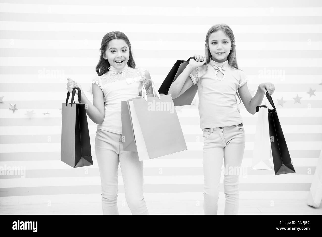 Girlish happiness. Kids happy carry bunch packages. Shopping with best friend concept. Girls like shopping. Kids happy small girls hold shopping bags. Enjoy shopping with best friend or sister. - Stock Image