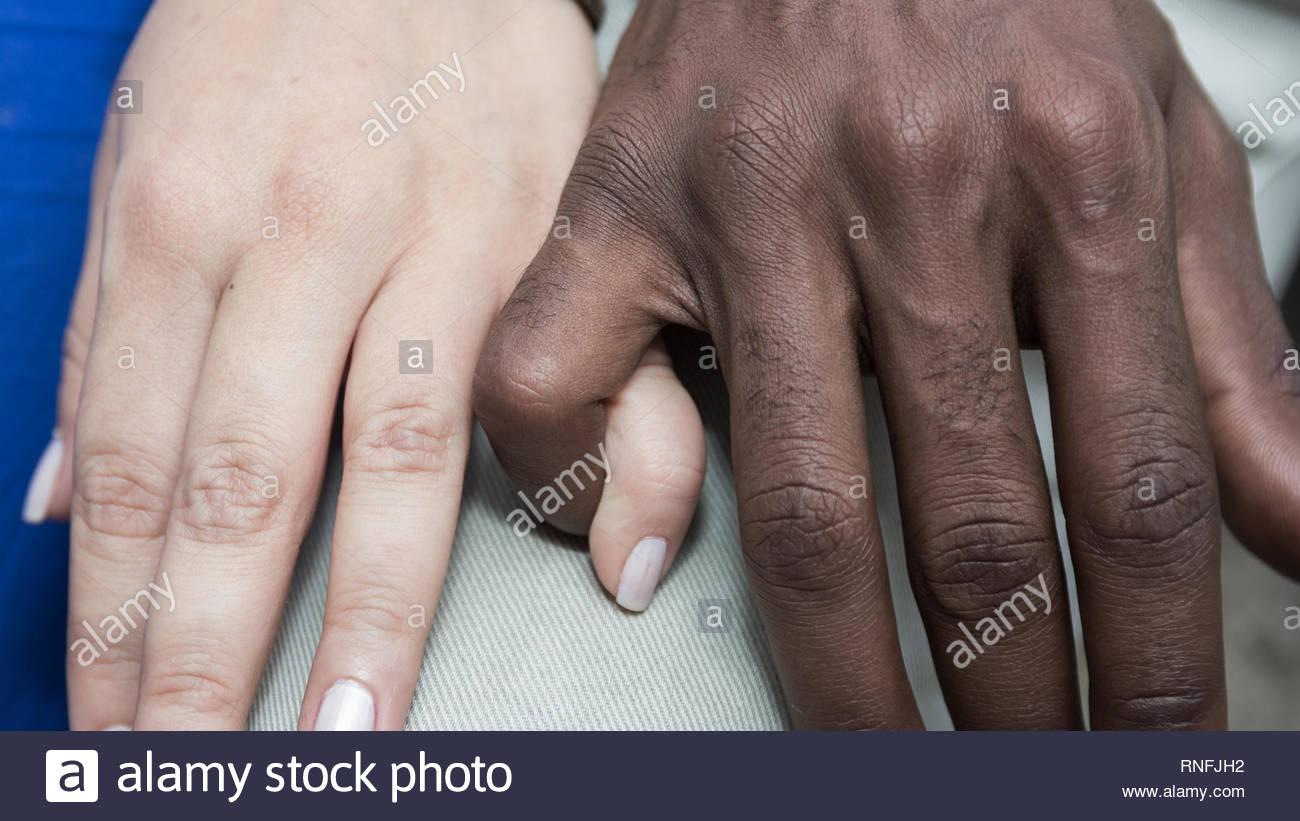 Romantic multiethnic couple. Holding pinky finger. Closeup hands. - Stock Image