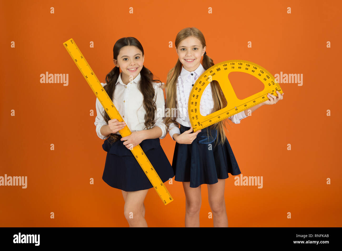 Geometry favorite subject. Education and school concept. School students learning geometry. Kids school uniform on orange background. STEM school disciplines. Pupil cute girls with big rulers. - Stock Image