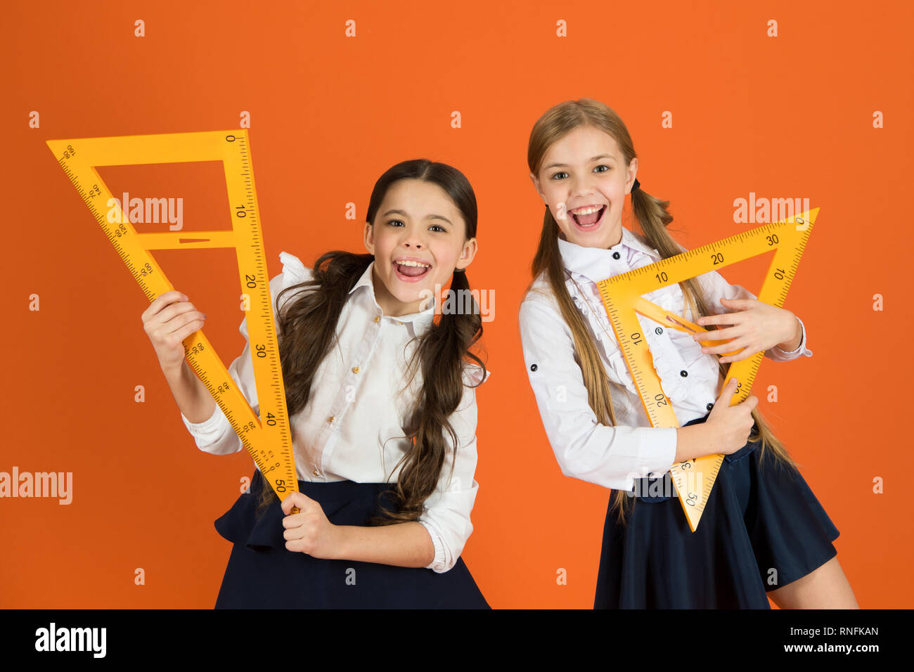 School students learning geometry. Kids school uniform on orange background. Pupil cute girls with big rulers. Geometry school subject. Drawing with ruler chalkboard. Education and school concept. - Stock Image