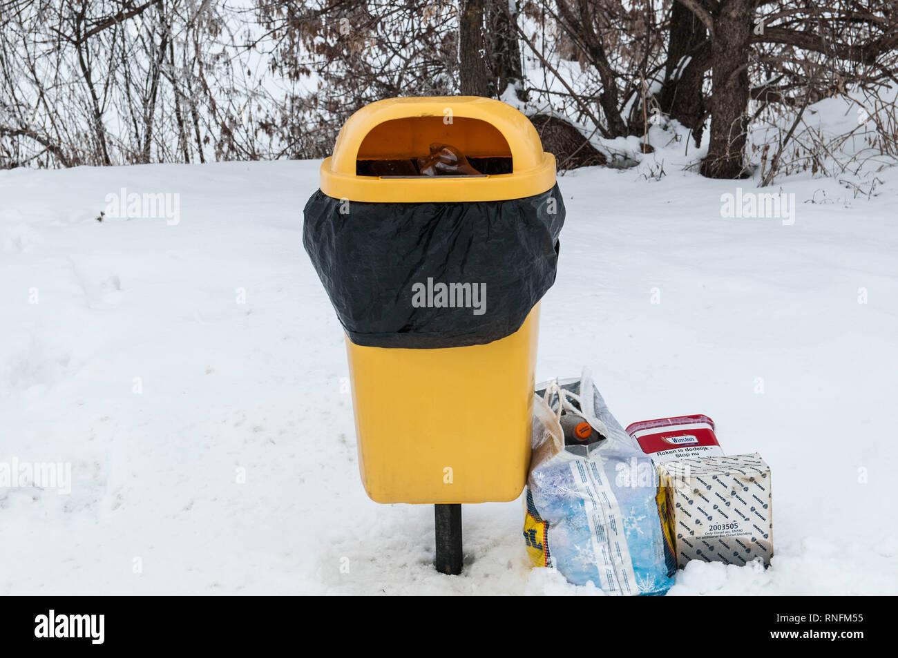 A full trashbin near roadside, plastic bags filled with trash - Stock Image