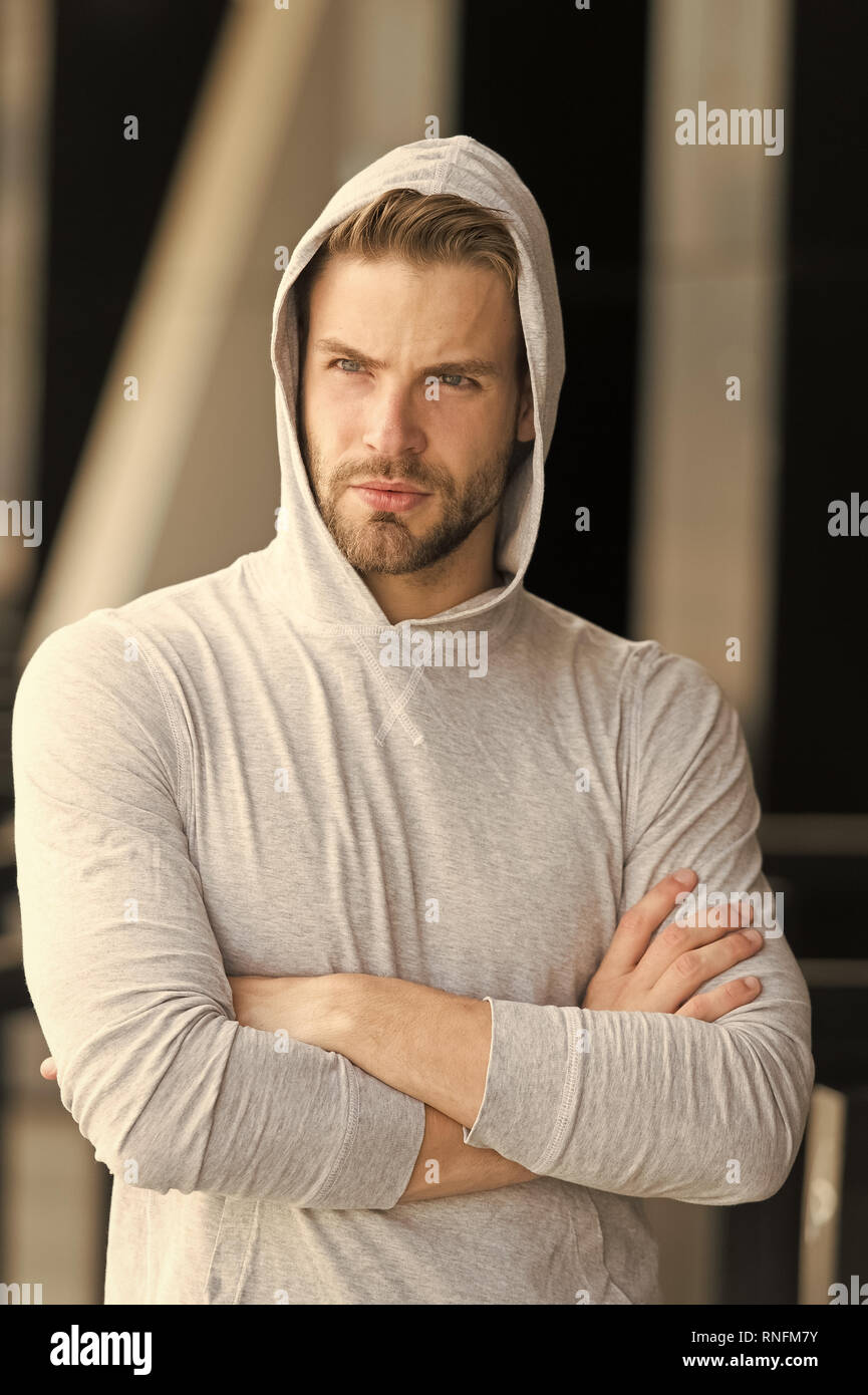 Cool and confident. Man unshaven hooded folded arms looks handsome and cool. Guy bearded attractive cares about appearance. Man bristle serious face, urban background, defocused. Metrosexual concept. - Stock Image