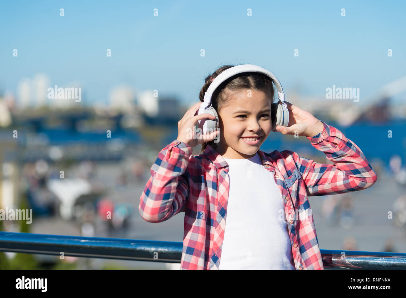 Girl child listen music outdoors with modern headphones. Kid little girl listen song headphones. Music account playlist. Customize your music. Discovering new music styles is great way into culture. - Stock Image