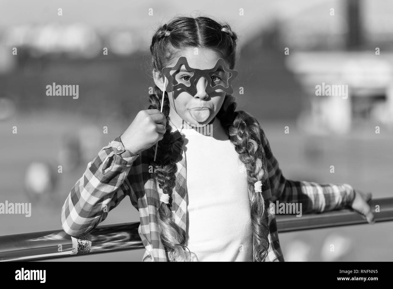 Getting ready for party. Small naughty girl having fun. Fashionable glasses for celebration. Stylish look. Disobedient small girl showing her tounge. Positive moments. Concept of childish carelessness. - Stock Image