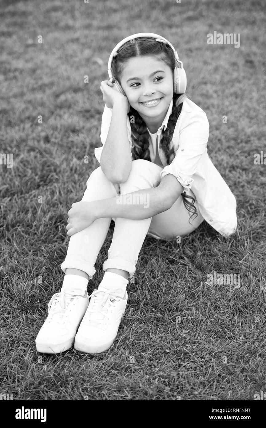 Positive influence of music. Child girl enjoying music modern earphones. Childhood and teenage music taste. Little girl listening music enjoy favorite song. Girl with headphones nature background. Stock Photo