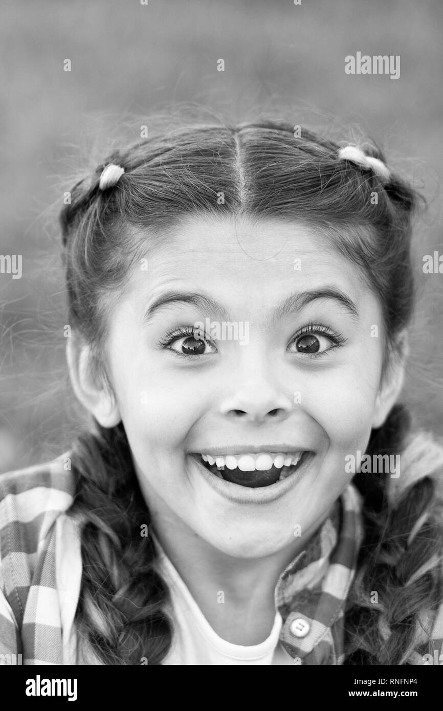 Cute surprised girl with smile on her face. Expression of happiness. Moment of unexpectancy. Looking forward to present. Beautiful young face. Bright emotion on lady face. Stock Photo