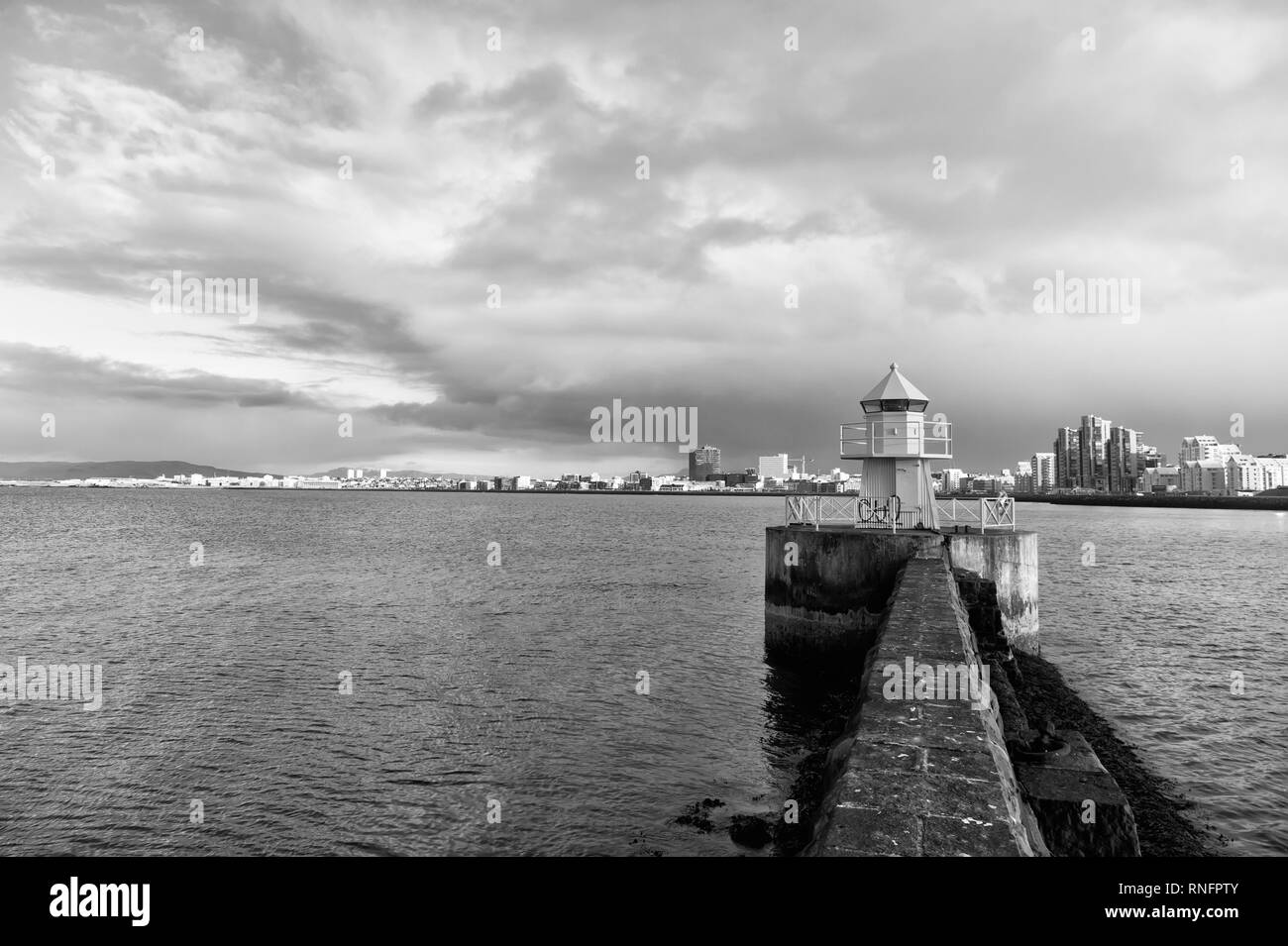 Sea port navigation concept. Sea transportation and navigation. Lighthouse on sea pier in reykjavik iceland. Lighthouse yellow bright tower at sea shore. Seascape and skyline with bright lighthouse. - Stock Image
