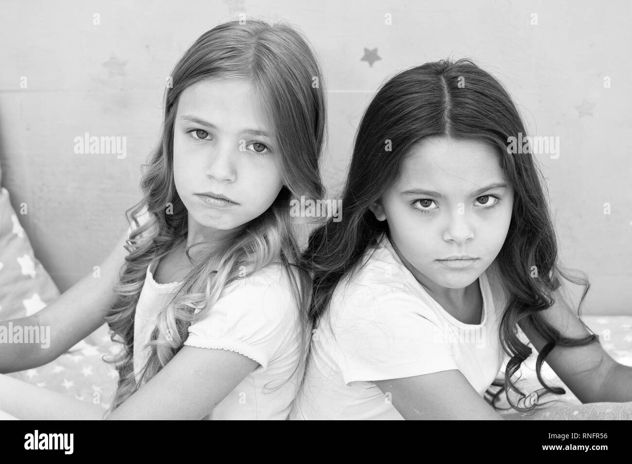 Offended feelings. Children offended keep silence. Relations sisters or best friends. Overcome relations issues. Childhood friendship. Friends sit back to back. Offended kids look seriously and sadly. - Stock Image