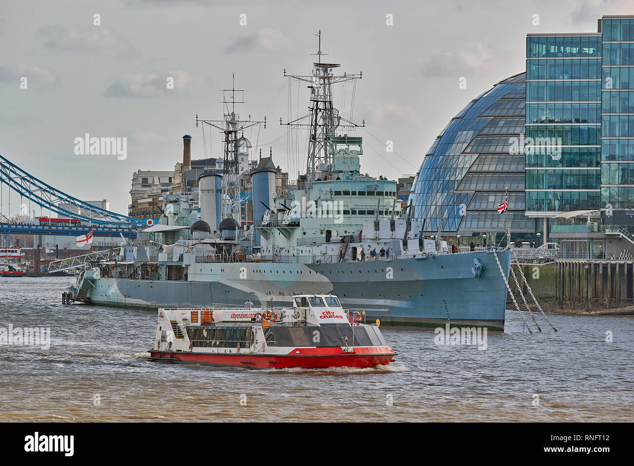 LONDON RIVER THAMES HMS BELFAST AND CITY CRUISE BOAT ON THE WATER - Stock Image