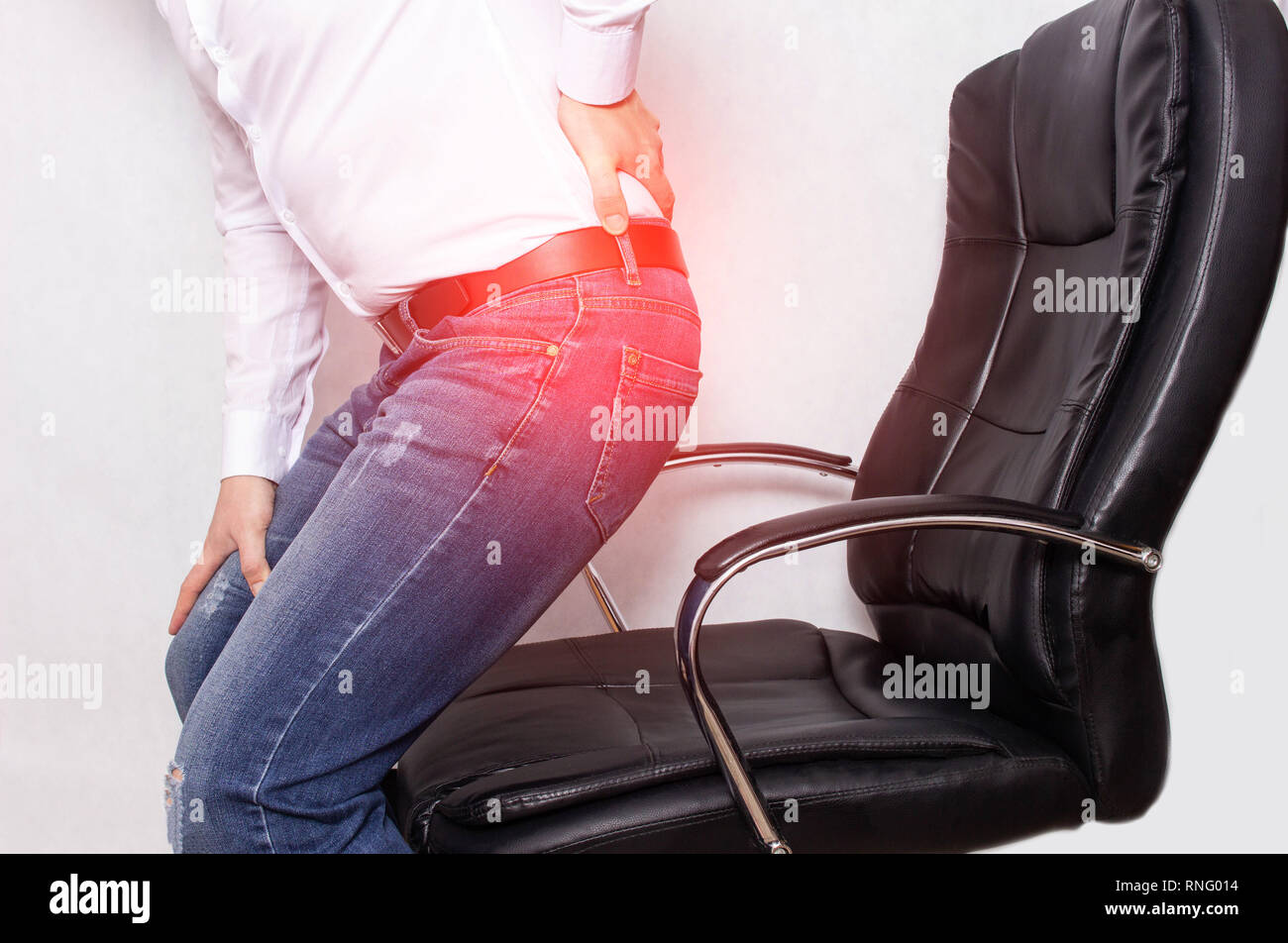 A man in the office holding his back from a chair, the concept of back pain, intervertebral hernia and osteochondrosis of the spine, myofascial syndro - Stock Image