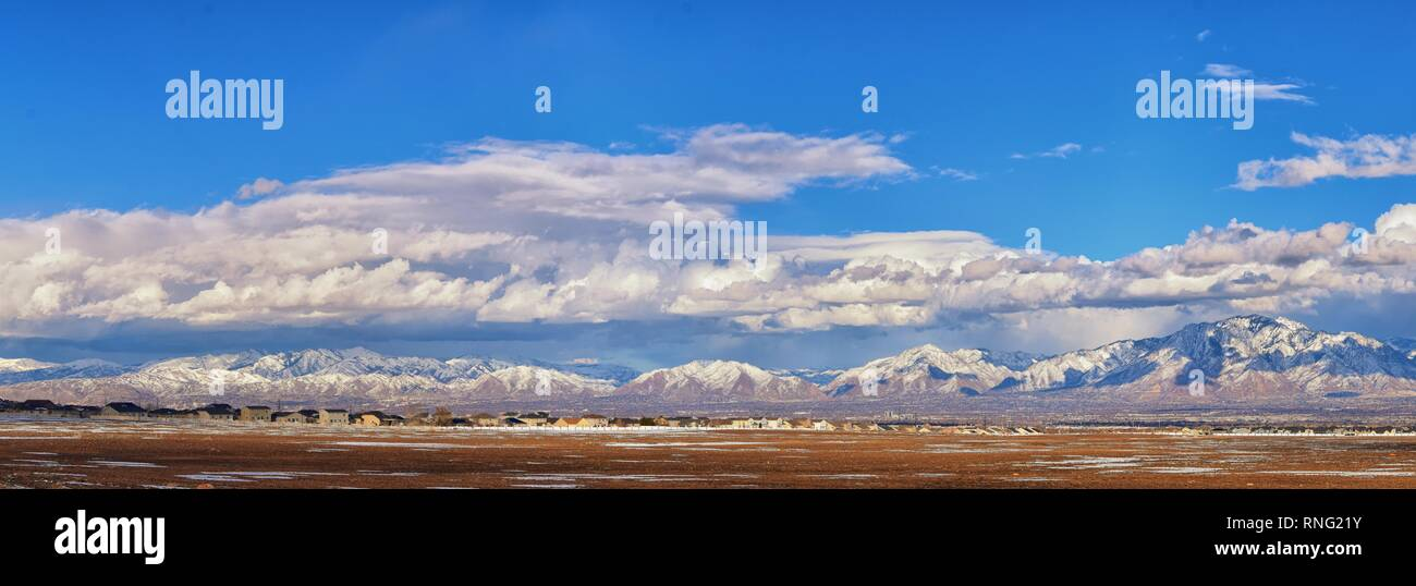 Winter Panoramic view of Snow capped Wasatch Front Rocky Mountains, Great Salt Lake Valley and Cloudscape from the Bacchus Highway. Utah, USA. Stock Photo