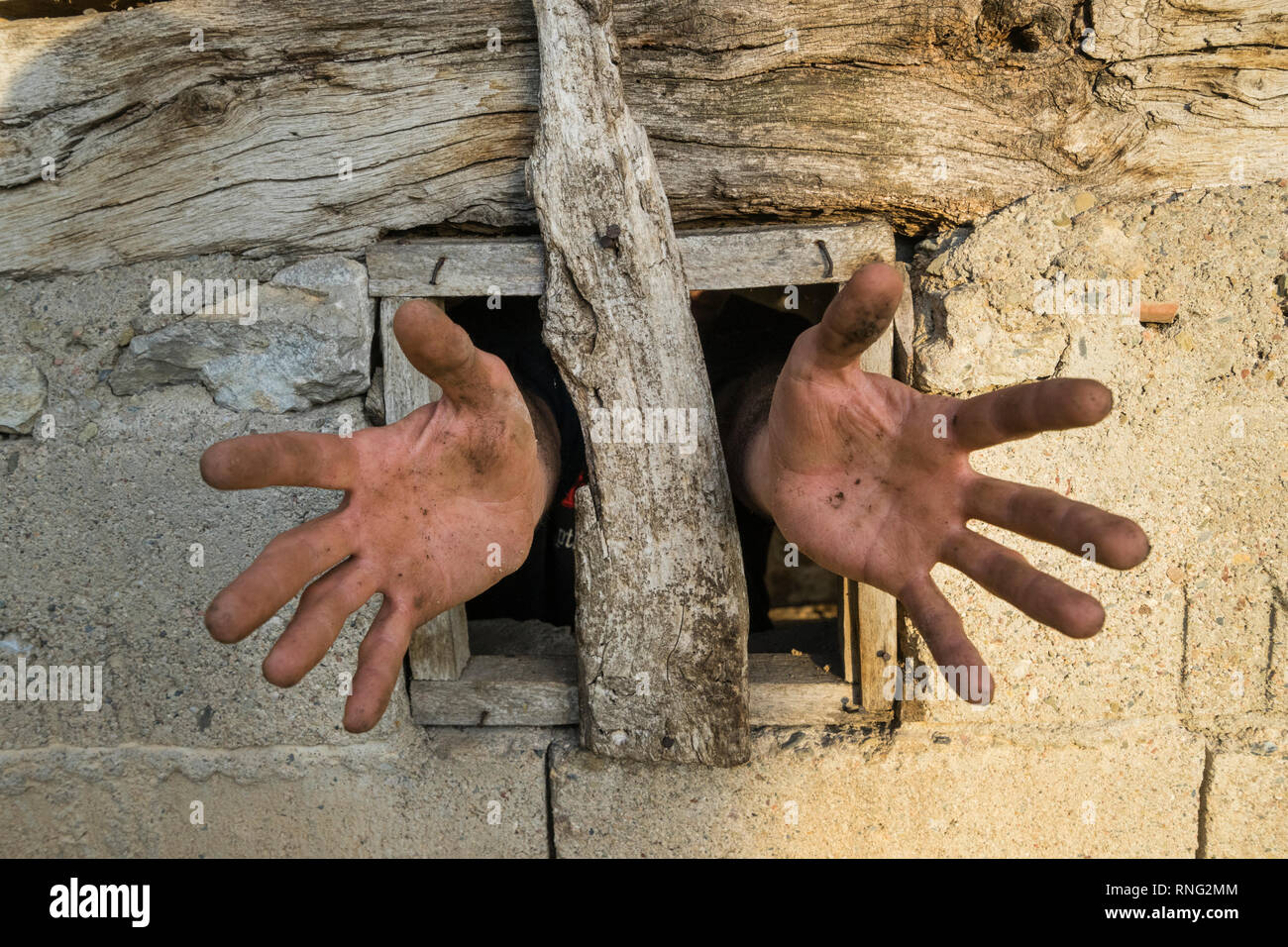Hands reaching out of a small window from a mud and stone made house in the Balkan Mountains region of Eastern Serbia. - Stock Image