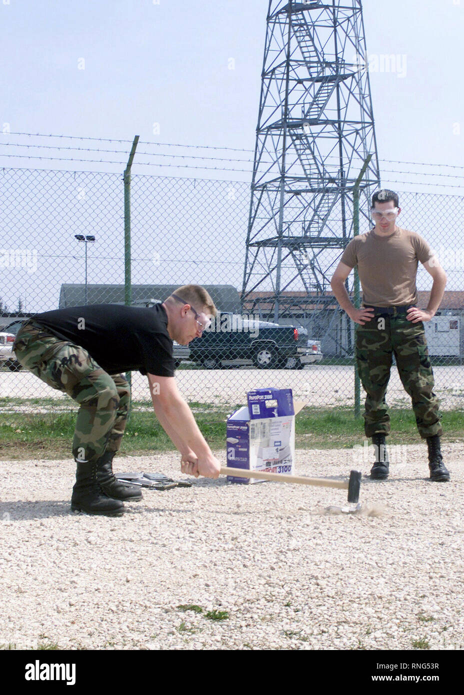 United States Air Force (USAF) Airman First Class (A1C) Jason Hirst, assigned to the 31st Communications Squadron (CS), Aviano Air Base, Italy, smashes a computer hard drive with a sledge hammer in order to render destroy it, as A1C Aaron Billingsley, observes. - Stock Image