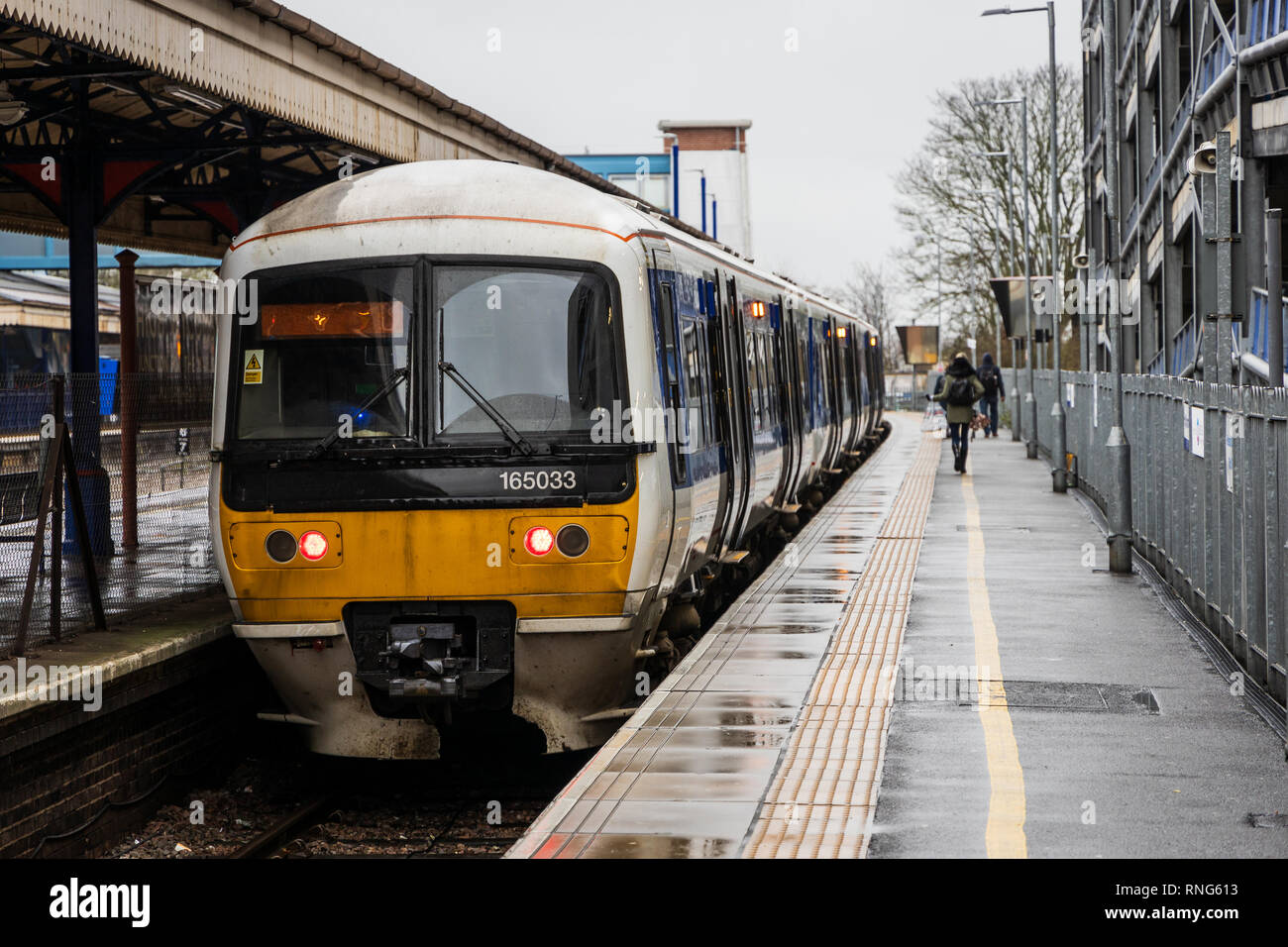 Commuters are running on a platform to a Chiltern Railways train from High Wycombe station to London during rush hour on a rainy winter morning - Stock Image