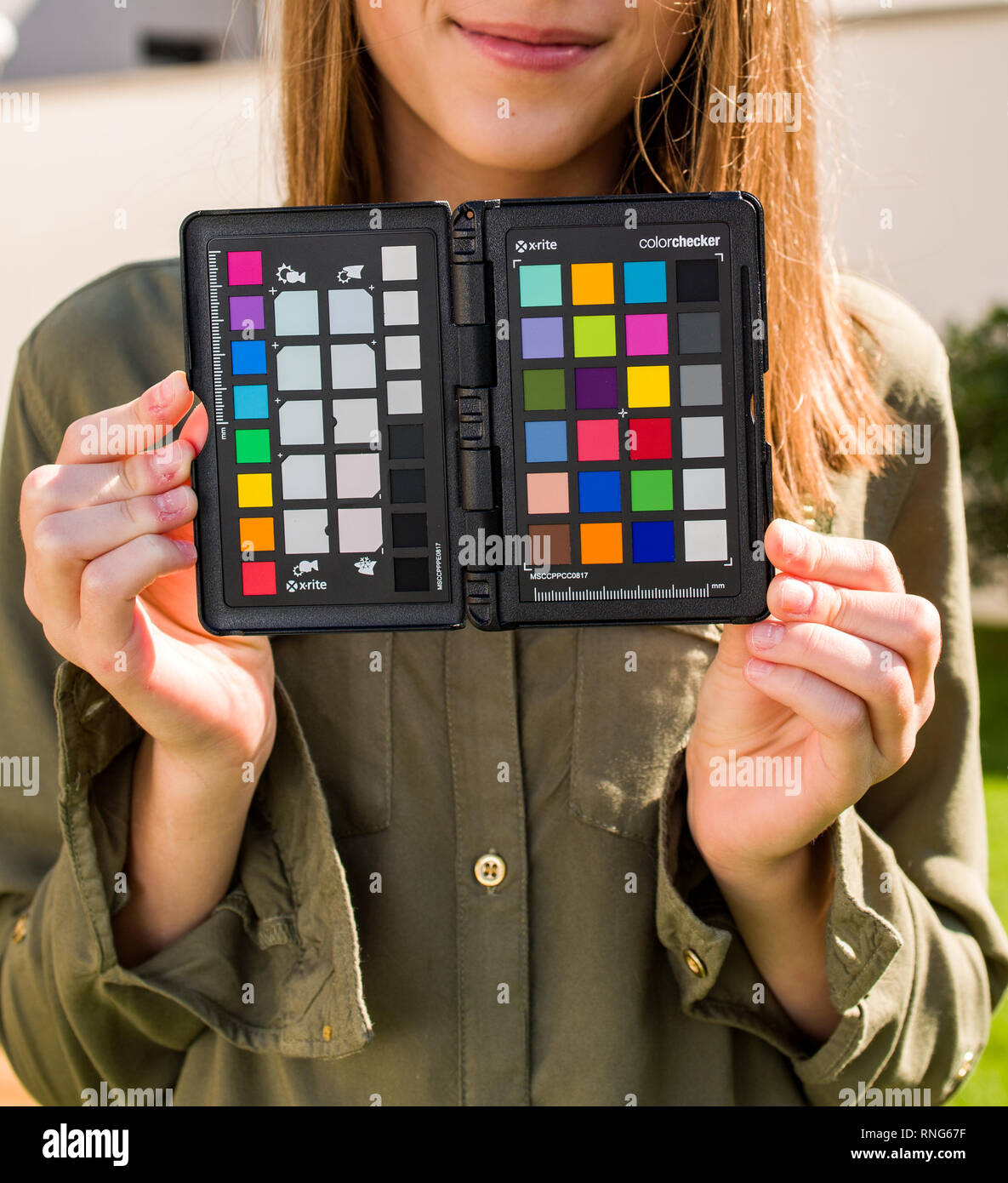 PARIS, FRANCE - SEP 30, 2018: Professional model holding Color Passport by X-Rite Color Reference Targets and camera calibration sfotware before the professional photo session shooting Stock Photo