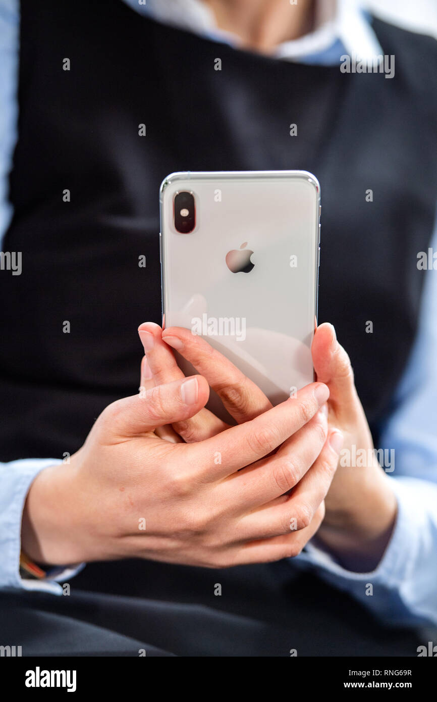 PARIS, FRANCE - OCT 2, 2018: business woman holding silver new Apple iPhone Xs Max smartphone telephone from Apple Computers with all home apps on OLED display Stock Photo