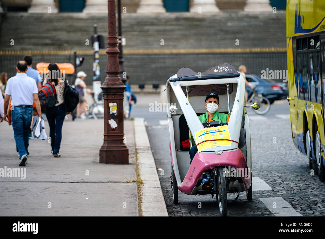 PARIS, FRANCE - MAY 21, 2016: Man with protection mask driving his rickshaw on Paris street - high level of air pollution and bad environment in central Paris, public transportation  - Stock Image