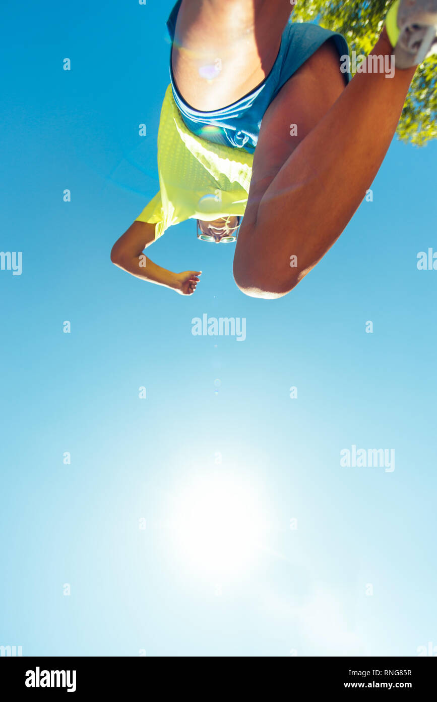 Muscles woman legs while jogging in the park Stock Photo