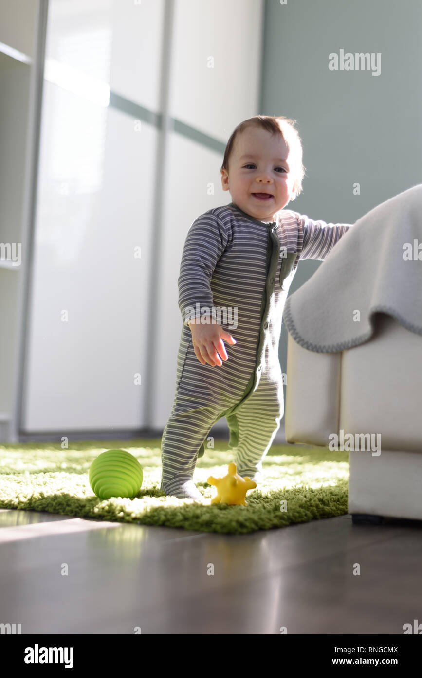 Standing boy on green carpet closeup. First step concept - Stock Image