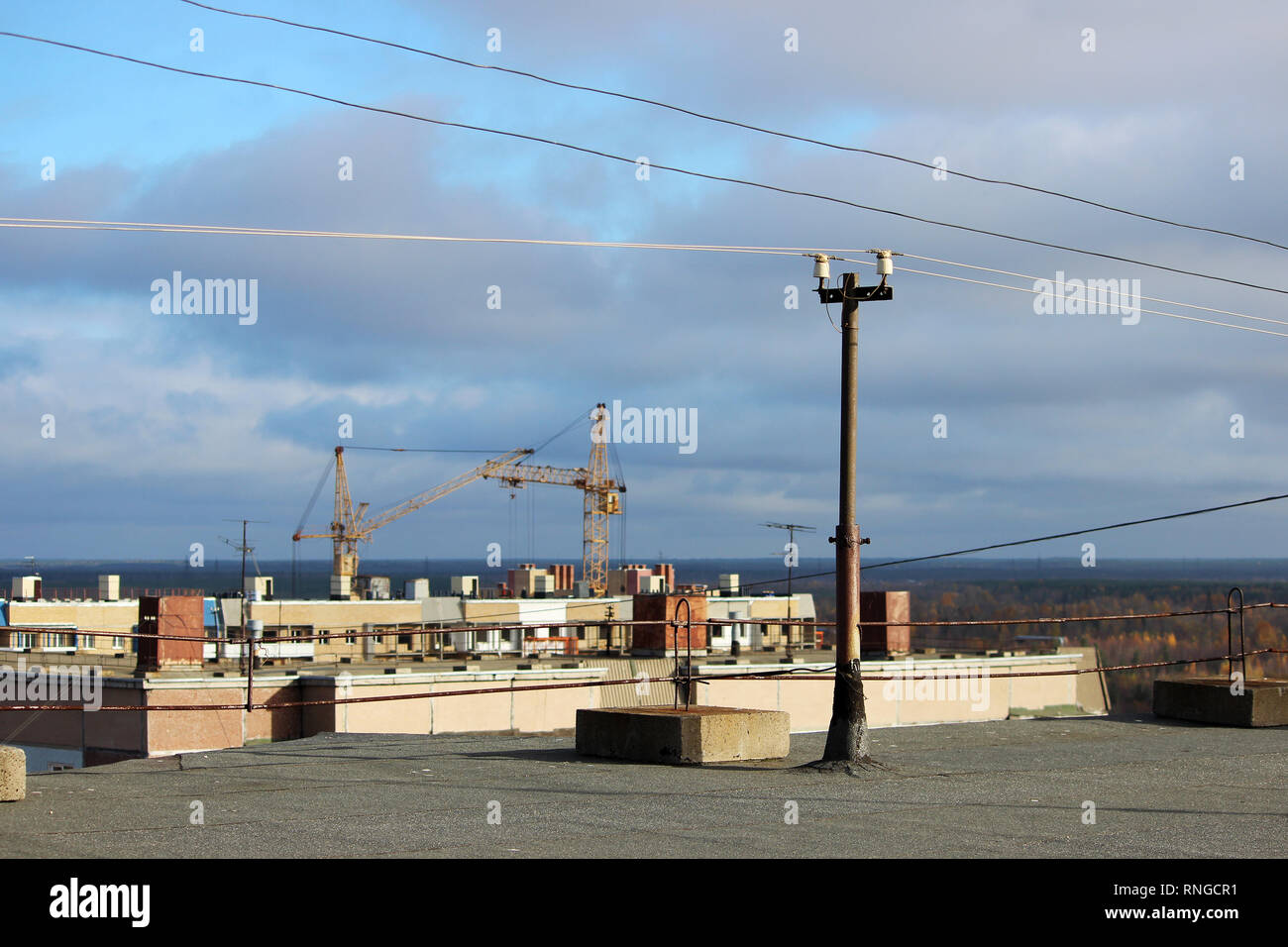 view from the flat roof of a multistory building covered with ruberoid, railing. column with electrical wires. view of the city of Arkhangelsk - Stock Image