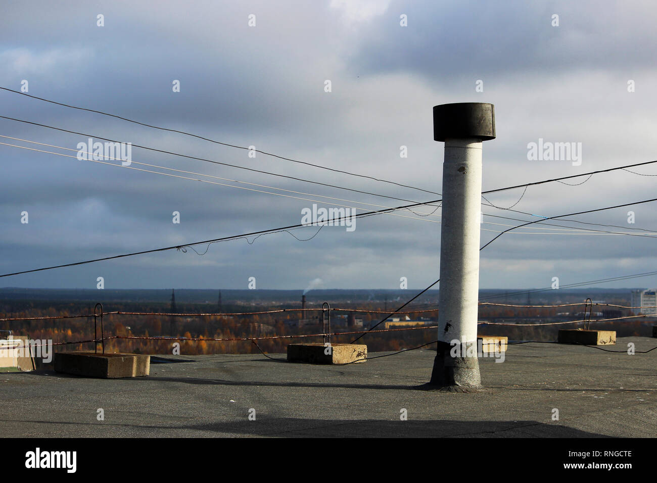 view from the flat roof of a multistory building covered with ruberoid, railing. ventilation tube. view of the city of Arkhangelsk - Stock Image