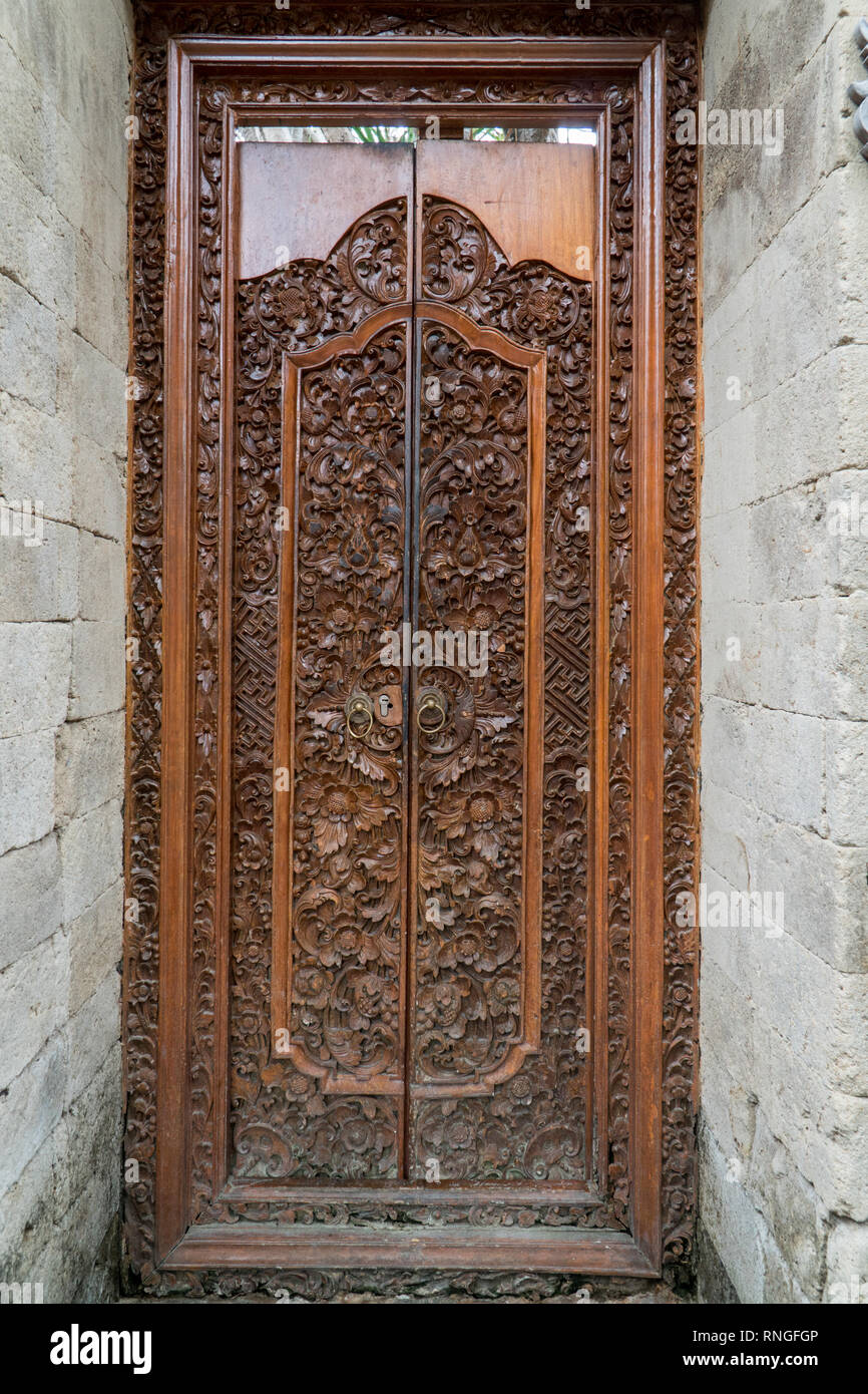 Balinese wood carved doors with traditional local ornaments. Local traditions and craftmanship concept - Stock Image