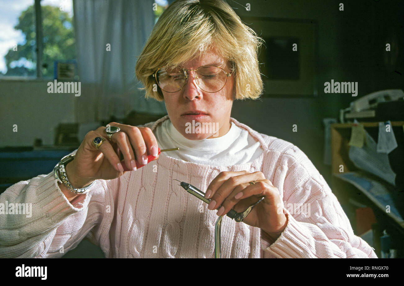 A young woman ties hand-made trout flies on a fly tying vice in Santa Fe, New Mexico. Stock Photo