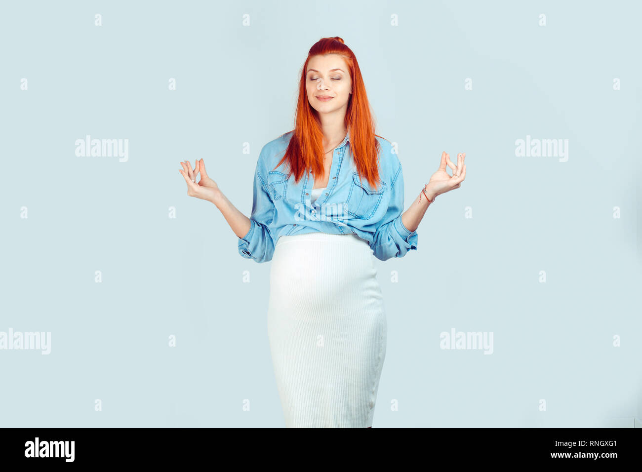 Young redhead pregnant woman in denim shirt holding hands apart and meditating taking breath before child birth isolated on blue. Stock Photo