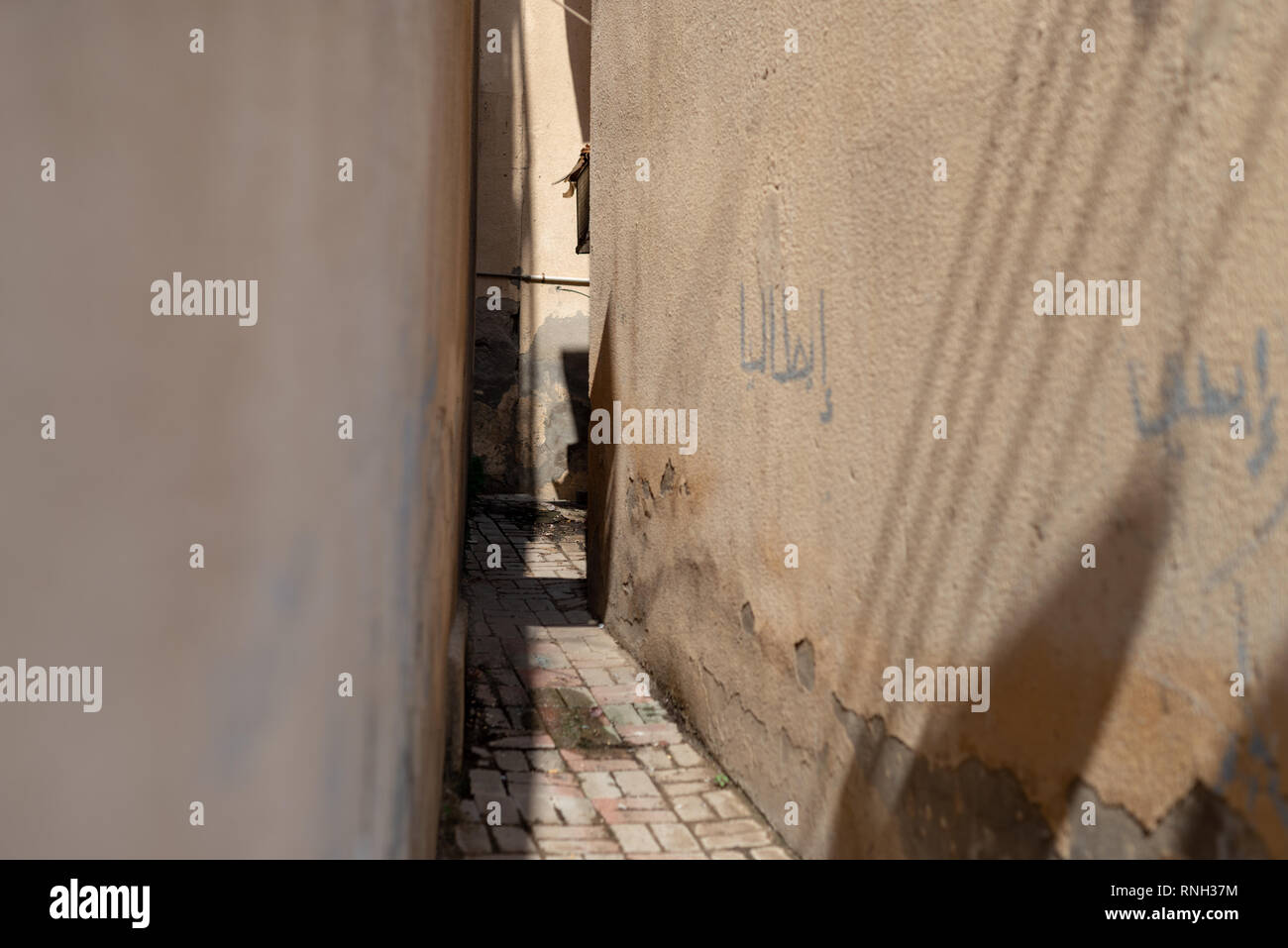 Narrow lane with graphitis in the historical district of Matrah, City of Muscat, Sultanate of Oman. - Stock Image