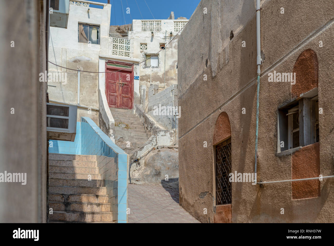 Starecases and red door in the historical district of Matrah, City of Muscat, Sultanate of Oman. - Stock Image