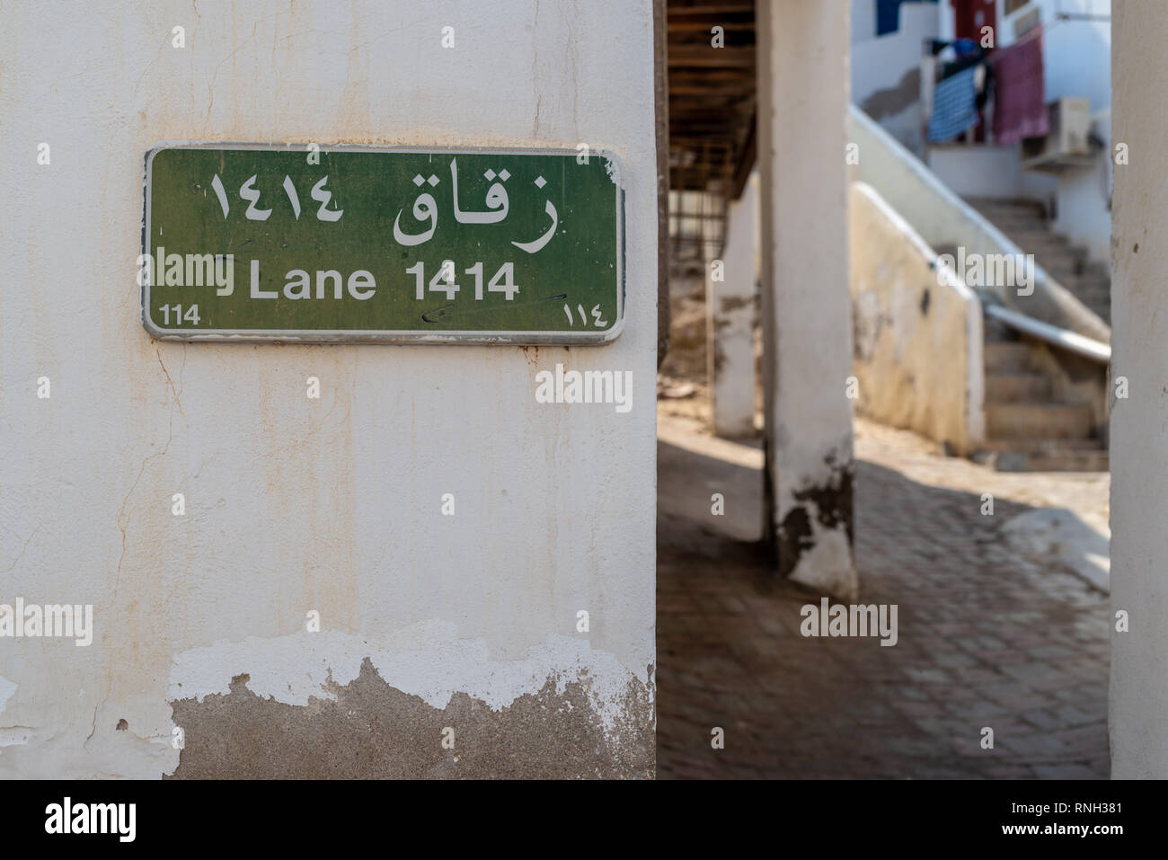 Street sign and number in the historical district of Matrah, City of Muscat, Sultanate of Oman. - Stock Image