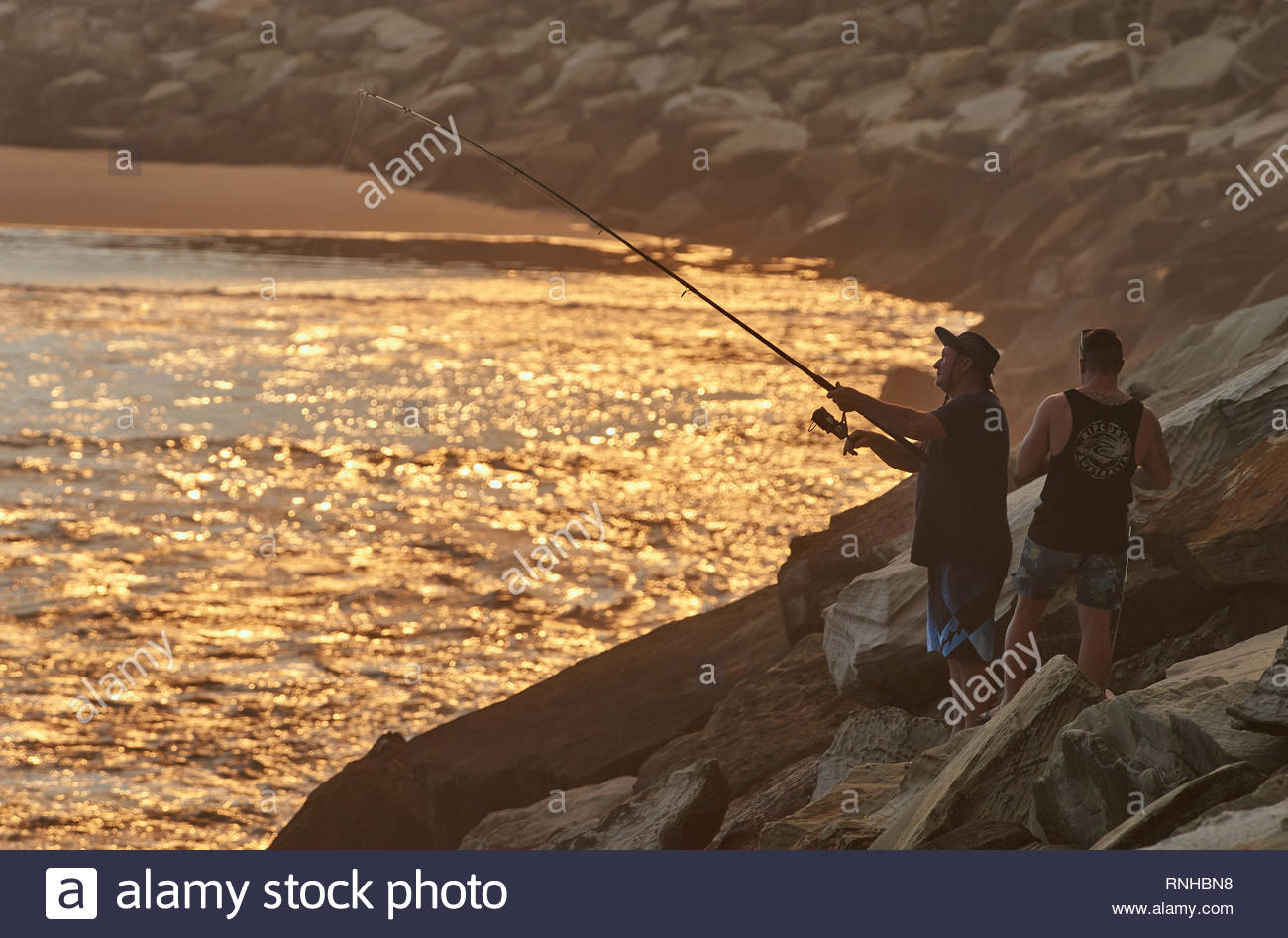 Yamba, NSW / Australia.  A rock-fisherman, casting his line into the Pacific Ocean, from the large rocky breakwall he's standing on with his friend. - Stock Image